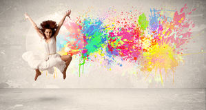 Happy teenager jumping with colorful ink splatter on urban backg Royalty Free Stock Photography