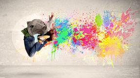 Happy teenager jumping with colorful ink splatter on urban background. Concept royalty free stock photo