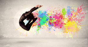 Happy teenager jumping with colorful ink splatter on urban backg Royalty Free Stock Images