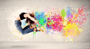 Happy teenager jumping with colorful ink splatter on urban backg Stock Images