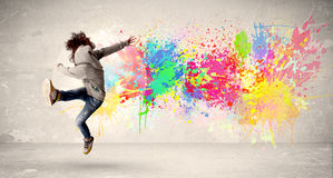 Happy teenager jumping with colorful ink splatter on urban backg Royalty Free Stock Image