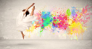 Happy teenager jumping with colorful ink splatter on urban backg. Round concept Stock Photos