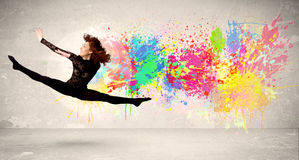 Happy teenager jumping with colorful ink splatter on urban backg. Round concept Royalty Free Stock Photography