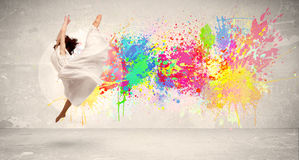 Happy teenager jumping with colorful ink splatter on urban backg. Round concept royalty free stock image