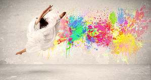 Happy teenager jumping with colorful ink splatter on urban backg. Round concept Royalty Free Stock Photo