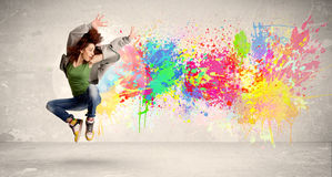 Happy teenager jumping with colorful ink splatter on urban background. Concept stock images