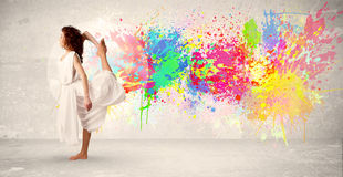Happy teenager jumping with colorful ink splatter on urban background. Concept royalty free stock images