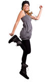 Happy Teenager Jumping Up. Exuberant Teenage Girl Wearing Fashionable Clothing Jumping For Joy on Isolated White Background Stock Images