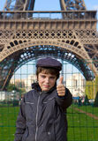 Happy teenager kid on front of Eiffel Tower, Paris. Cheerful smiling teenager kid tourist showing thumbs up success sign in front of Eiffel Tower, Paris Royalty Free Stock Photos