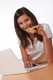Happy teenager with laptop eating protein bar. Happy teenager with laptop holding protein bar on wooden floor Royalty Free Stock Photos
