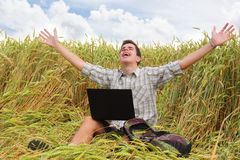 Happy teenager with a laptop in the field. royalty free stock images