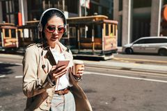 Happy teenager listening music wearing headphones. On the street. old famous cable car streetcar in background driving. young college student girl in earphones stock photography