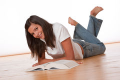 Happy teenager lying down with book Stock Photo