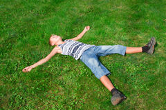Happy teenager lying on the grass Stock Photos