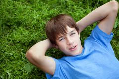 Happy teenager lying on grass in park Stock Photos