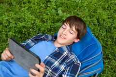 Happy teenager lying on grass in park Stock Photo