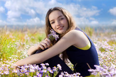 Happy teenager on the meadow with flowers Stock Image