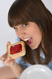 Happy teenager in pajamas eating healthy toast Royalty Free Stock Images