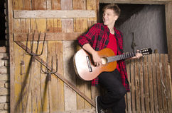Happy teenager playing acoustic guitar concept. Leaning on old wooden barn door Stock Photography