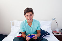 Happy teenager playing video games in his bedroom. Attractive happy teenager playing video games in his bedroom Royalty Free Stock Photography