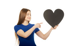 Happy teenager pointing on paper heart. Royalty Free Stock Photography
