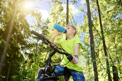 Happy teenager rides a bicycle in pine wood, in sunny day. Stock Photography