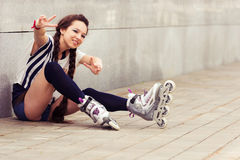 Happy teenager on rollerblading sitting on street Stock Image