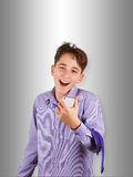 Happy teenager in shirt and tie listening to music, typing on mobile phone or making selfie Royalty Free Stock Photography
