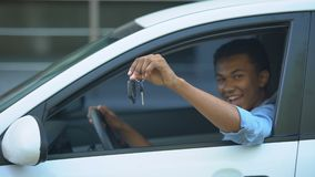 Happy teenager showing car key to window sitting on driver seat of new vehicle. Stock footage stock video footage
