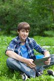 Happy teenager siting on grass in park Royalty Free Stock Image