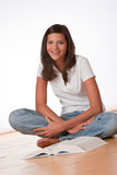 Happy teenager sitting with book. On wooden floor Royalty Free Stock Photography