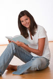 Happy teenager sitting with book. On wooden floor Stock Photo