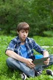 Happy teenager sitting on grass in park Stock Photos