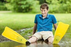 Happy teenager sitting in large puddle Royalty Free Stock Photos