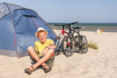 Happy teenager is sitting near the tent at the bea Royalty Free Stock Photography