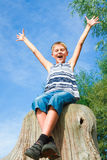 Happy teenager sitting on a stump Royalty Free Stock Photography