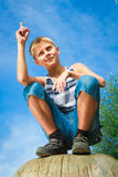 Happy teenager sitting on a stump Royalty Free Stock Photos