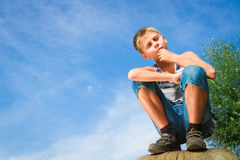 Happy teenager sitting on a stump Royalty Free Stock Photo
