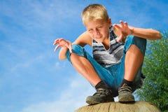 Happy teenager sitting on a stump Stock Photos