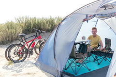 Happy teenager is sitting in the tent at the beach Stock Photo