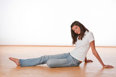 Happy teenager sitting on wooden floor Stock Photos