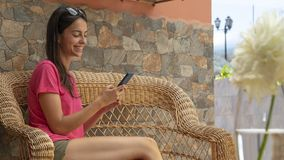 Free Happy Teenager Smiling, Sending Message By Cellphone. Good Looking Girl Sitting In Wicker Couch Chatting With Friends. Woman Stock Image - 157009811