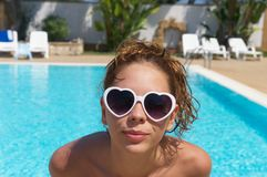 Happy teenager in a swimming pool on holidays. An happy teenager wearing nice white heart-shape glasses is having fun swimming in a pool of a sicilian resort Royalty Free Stock Photos