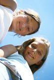 Happy teenagers. A portrait of two smiling teenage girls looking down at the camera Stock Photography