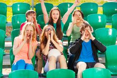 Happy teenagers cheer for the team during game. At the stadium sitting on the tribune outside in summer royalty free stock image