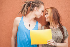 Happy teenagers couple looking and holding frame at red background Stock Photography