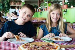 Happy teenagers eating pizza in a cafe. Friends or siblings having fun in restaurant stock photos