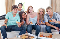 Happy teenagers eating pizza in the living-room. On the sofa Royalty Free Stock Photos