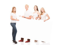 Happy teenagers holding a blank white banner. Group of teenagers with a blank, white billboard isolated on white Stock Image