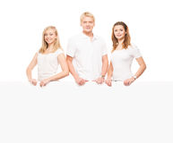 Happy teenagers holding a blank white banner. Group of teenagers with a blank, white billboard isolated on white Stock Images